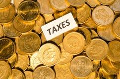 Taxes sign on golden coins Stock Photos