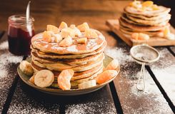 Stack of golden pancakes with bananas and oranges on wooden board covered with caster sugar. Heap of american pancakes with maple. Syrup and a glass of jam in royalty free stock images