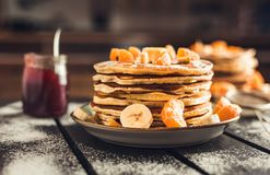 Stack of golden pancakes with bananas and oranges on wooden board covered with caster sugar. Heap of american pancakes with maple. Syrup and a glass of jam in royalty free stock photo