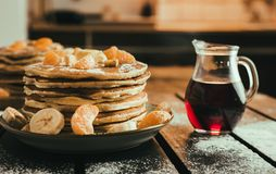 Stack of golden pancakes with bananas and oranges on wooden board covered with caster sugar. Heap of american pancakes with a jug. Full of syrup in kitchen stock images