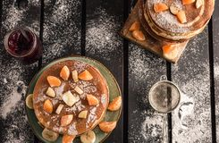 Stack of golden pancakes with bananas and oranges on wooden board covered with caster sugar top view Heap of american pancakes. With fruit syrup and a glass of stock image