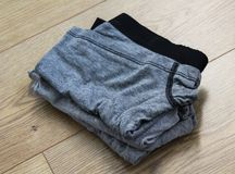 Stack of gray male underwear on wooden background. Close up stack of underwear on wooden table Royalty Free Stock Image