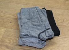 Stack of gray male underwear on wooden background. Close up stack of underwear on wooden table Royalty Free Stock Images