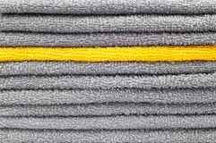 Stack of gray and yellow terry towels, conceptual background stock image
