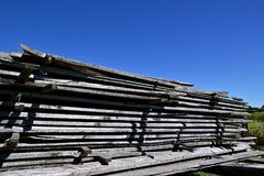 Stack of graying rough cut dimensional lumber. Weathered dimensional rough cut oak lumber is stacked outside with spacers allowing for air drying Royalty Free Stock Image
