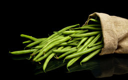 Stack of green beans in linen sack on black. Background Stock Image