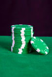 Stack of green chips on a green playing table Stock Image