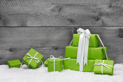 Stack of green Christmas presents, with snow on grey royalty free stock image