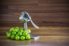 Stack of green lemon with aluminum manual juicer squeezer fruit Royalty Free Stock Photos