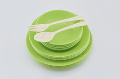 Stack of green plastic plate and dish with spoon  on whi Royalty Free Stock Photography