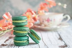 Stack of Green Tea Flavrored Macarons. Stack of fresh french green tea macarons on a white rustic table with flowers and antique tea cup blurred in background royalty free stock images