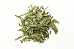 A stack of green tea leaves with tips on a white background stock image