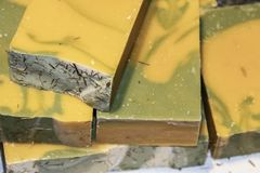 Stack of green and yellow marbled handmade soap with herbs showing royalty free stock photos