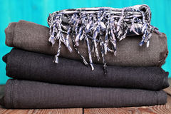 Stack of grey and black blue jeans with scarf on a wooden table Stock Images