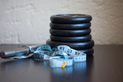 Stack of gym weight plates with a tape measure Royalty Free Stock Photo