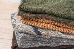 Stack of Hand Knitted Warm Winter Socks Scarfs Mittens From Coarse Wool Yarn Brown Beige Grey. Royalty Free Stock Photos