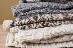Stack of Handmade Warm Knitted Socks Scarfs Mittens Sweaters From Rough Wool Yarn Brown Beige Grey. Wood Table Olive Color Wall royalty free stock images