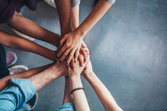Stack of hands showing unity and teamwork. Close up top view of young people putting their hands together. Friends with stack of hands showing unity and teamwork Royalty Free Stock Photo