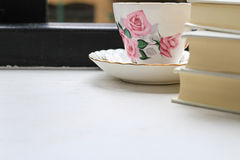 Stack of hardback books and cup of tea in china cup and saucer on a windowsill. Royalty Free Stock Photography