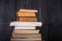 Stack of hardback books on dark wooden background. Back to school stock images