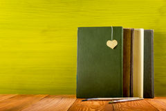 Stack of hardback books, diary on wooden deck table and green background. Back to school. Copy Space. Education Royalty Free Stock Photos