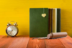 Stack of hardback books, diary on wooden deck table and yellow background. Back to school. Copy Space. Education Stock Images