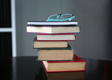 Stack of hardback books with glasses on wooden table. Education background royalty free stock photography