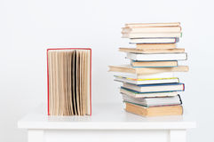 Stack of hardback books and old open book on white wall background. Search for relevant and necessary information. Stack of hardback books and old open book on royalty free stock image