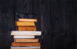 Stack of hardback books with reading glasses on dark wooden background. Back to school. Copy space royalty free stock photos