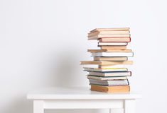 Stack of hardback books on the white table. Search for relevant and necessary information. Stack of hardback books on the white table on white wall background royalty free stock photos