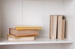 Stack of hardback books on wooden bookshelf. Back to school stock images
