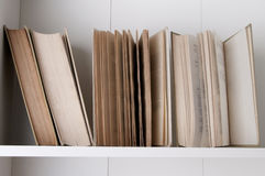 Stack of hardback books on wooden bookshelf. Open book, stack of hardback books on wooden bookshelf stock photo