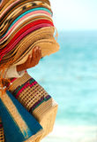 Stack of Hats for Sale. Stack of Straw hats and several straw bags on the arm of a beach vendor.  There is blue ocean and pale blue sky in the blurred background Royalty Free Stock Photography