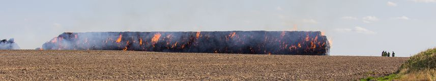 Stack hay in fire on field with firemans.  stock photo