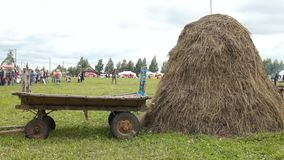 A stack of hay and cart. A stack of hay and old cart on festival stock video footage