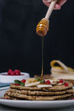 Stack of healthy low carbs oat pancakes honey motion Stock Photo