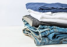 Stack Heap of Folded Jeans Cotton Pants Blue Shirts on White Wall Background. Closet Shelf. Eco Fashion Authentic Classic Style. Natural Materials. Unisex royalty free stock image