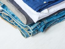 Stack Heap of Folded Jeans Cotton Pants Blue Shirts on White Wood Background. Closet Shelf. Eco Fashion Authentic Classic Style. Natural Materials. Unisex stock images