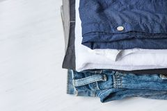 Stack Heap of Folded Jeans Cotton Pants and Shirts on White Wood Background Shelf Closet. Eco Fashion Authentic Classic Style. Natural Materials. Unisex Copy Stock Images