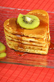 Stack of heart-shaped pancakes with syrup and kiwi fruit Royalty Free Stock Photography