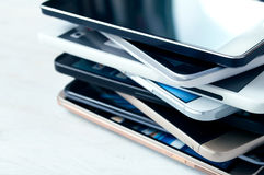 Stack of high-end smartphones. Stack of high-end smartphones on white wooden desk stock photos