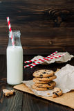 Stack of homemade chocolate chip cookies with milk on dark wooden table. Copy space background Royalty Free Stock Image