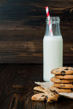 Stack of homemade chocolate chip cookies with milk on dark wooden table. Copy space background Royalty Free Stock Photography