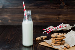 Stack of homemade chocolate chip cookies with milk on dark wooden table. Copy space background Stock Photos