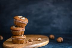 Stack of Homemade delicious muffin on dark background. Cup cakes with banana and walnut. Side view, copy space royalty free stock photos