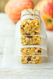 Stack of homemade muesli cereal bar with oats, nuts, raisins, honey and dried apples. Lined with parchment paper, tied with twine Stock Photo