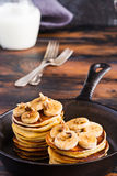 Stack of homemade pancakes with banana, maple syrup and walnuts in black cast iron skillet. Vintage forks, glass jar with milk, wooden rustic table royalty free stock image