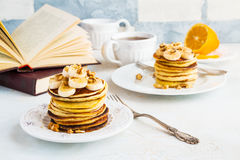 Stack of homemade pancakes with banana, maple syrup and walnuts on vintage plate. Fork, fresh sliced fresh lemon, cup of tea, open book, white and gray royalty free stock photos