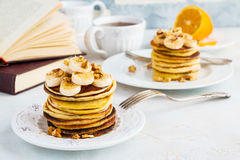Stack of homemade pancakes with banana, maple syrup and walnuts on vintage plate. Fork, fresh sliced fresh lemon, cup of tea, open book, white and gray royalty free stock photography