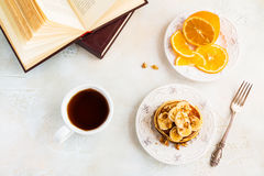 Stack of homemade pancakes with banana, maple syrup and walnuts on vintage plate. Fork, fresh sliced fresh lemon, cup of tea, white and gray concrete royalty free stock image
